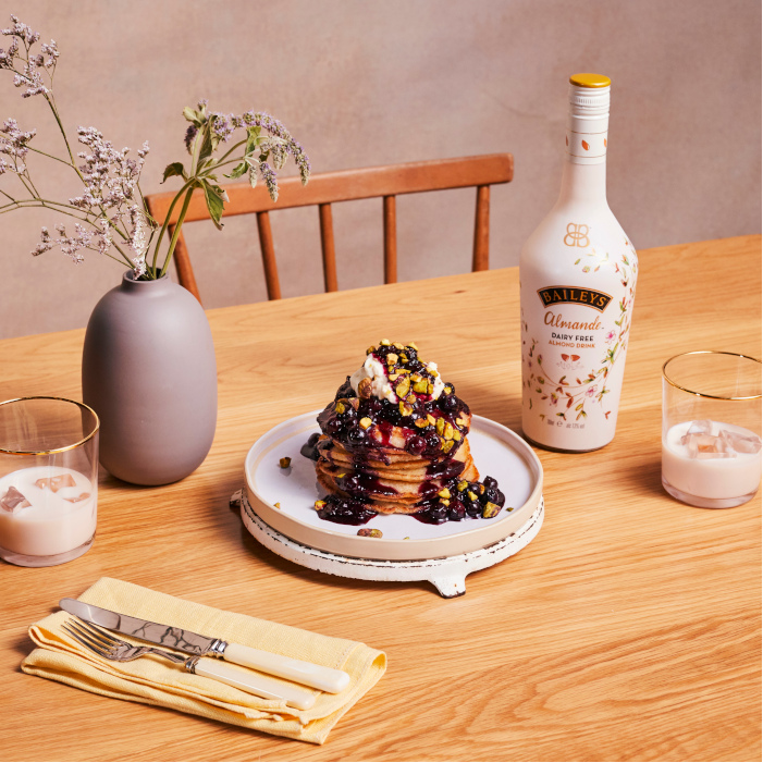 #Vegan #Blueberry, #Coconut #Almande and #Pistachio #Pancakes on a table next to a #bottle of #Almond #Baileys