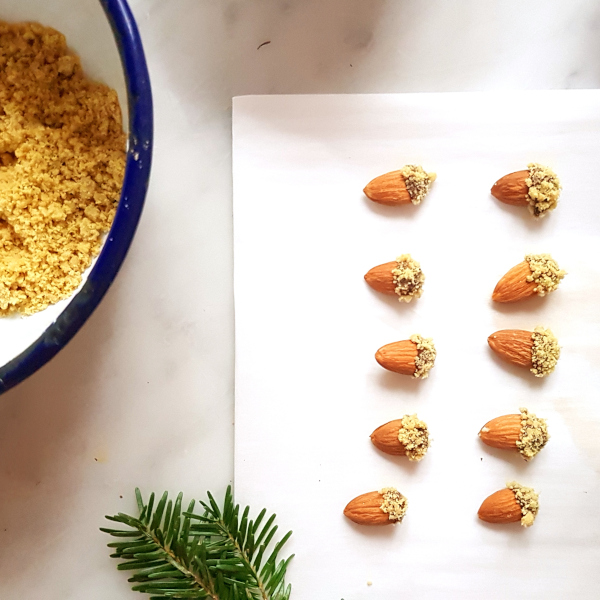 Almonds acorns dipped in crumble and set out on a marble table with pine decoration