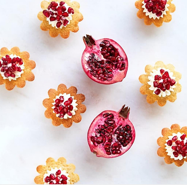 pomegranate and black tea vegan cakes around a cut pomegranate set on a marble table