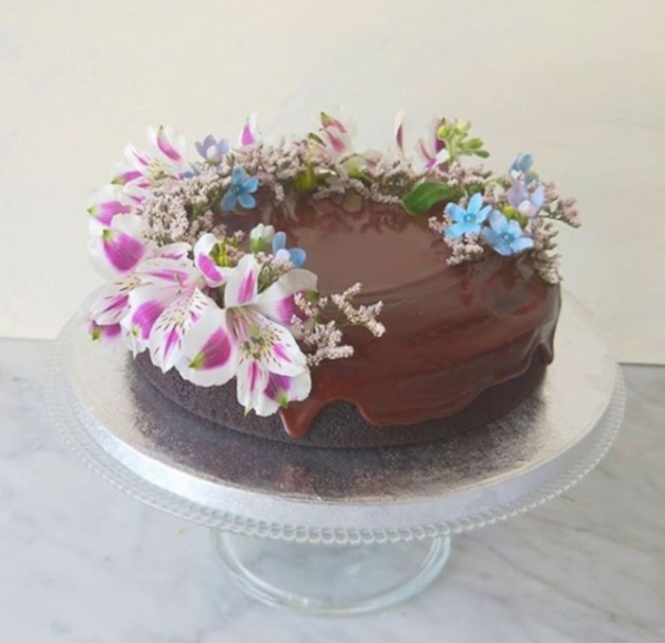 Vegan chocolate cake with chocolate ganache and floral decorations